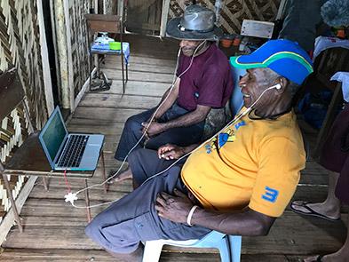 Ayasilo Heina and Gigiyo Weinabe watch playback of the film, Bona Village, Bosavi, December 2019